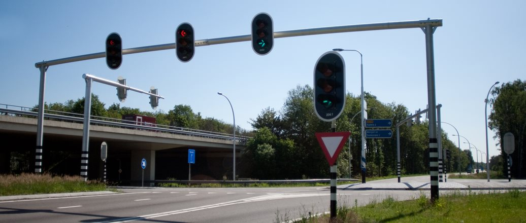 an intersection. traffic lights hanging on a pole across the road