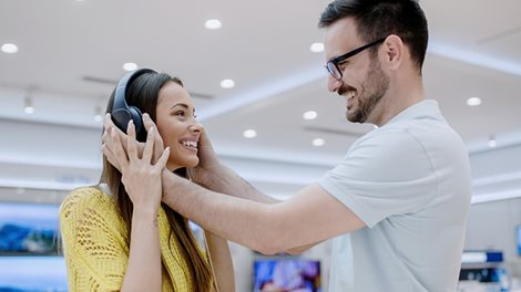 Young couple testing headphones in a tech store