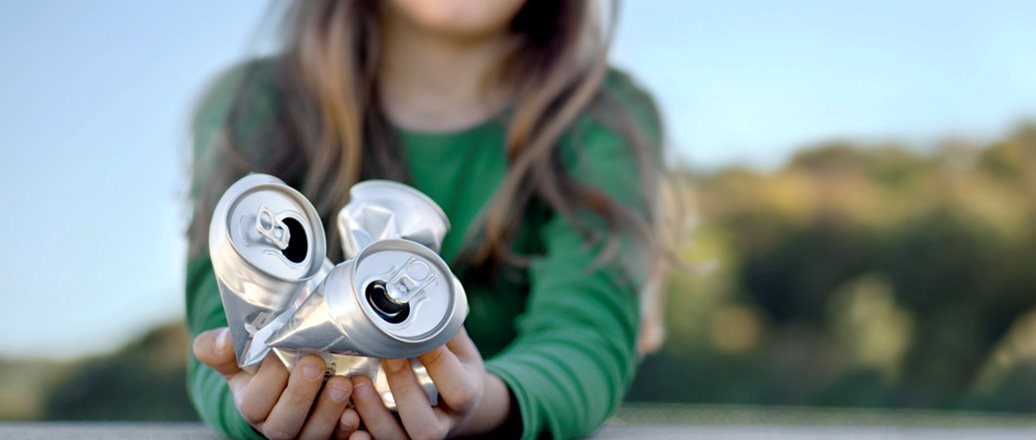 Girl holding crumpled aluminium cans