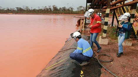 people inspecting a red mud deposit