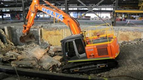 Orange excavator operating inside a building