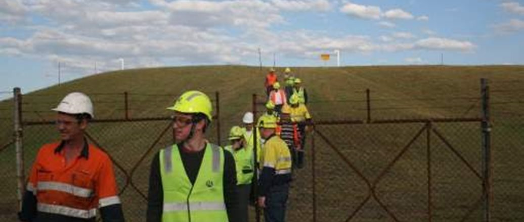 people in protective helmets and reflective vests in a field