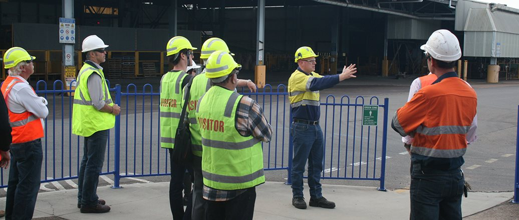 group of people in protective gear outside the plant gates