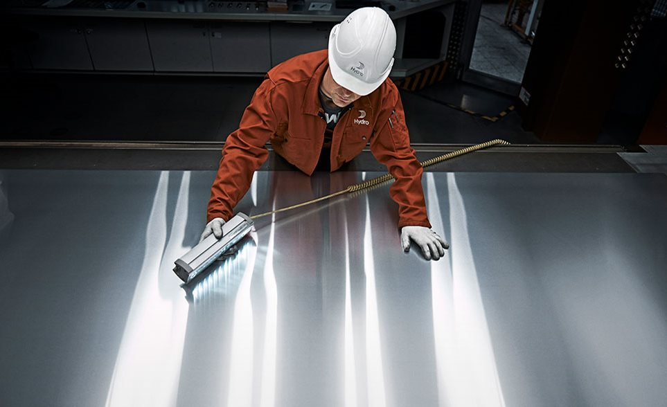 worker inspecting aluminum plate