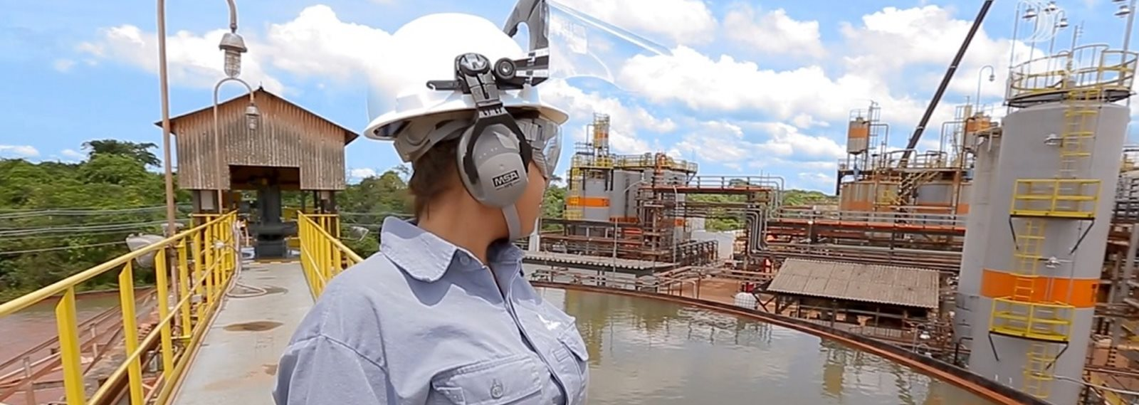 Alunorte's female employee stands watching the company's water treatment facility plant in the background