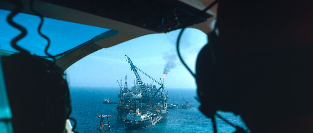 View of marine oil rig and tankers from helicopter cockpit