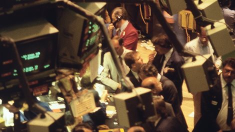 Men at the trading floor of New York Stock Exchange 1986, surrounded by screens.