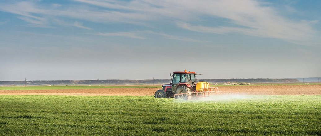 a tractor spraying a green field