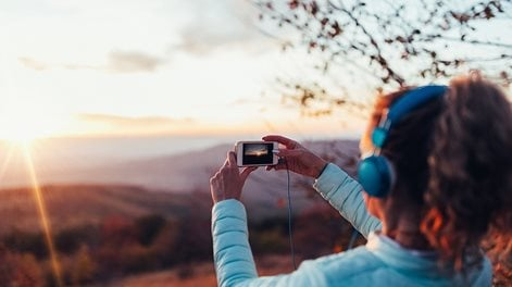 girl taking photo of sunset with smartphone